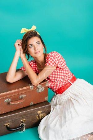 Photo pour Souriant, rêveur pin up femme appuyé sur des valises vintage sur turquoise - image libre de droit