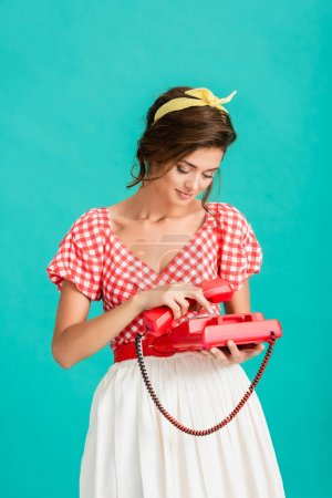 young woman in stylish retro clothes calling on vintage telephone isolated on turquoise
