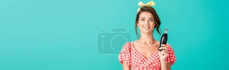 Photo for Smiling pin up woman with bottle of soda looking at camera isolated on turquoise, banner - Royalty Free Image