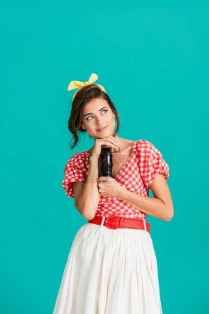 Photo pour Souriant, rêveuse pin up femme regardant loin tout en tenant bouteille de soda isolé sur turquoise - image libre de droit
