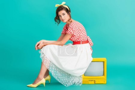 pretty woman in retro clothes looking at camera while sitting on yellow vintage tv set on turquoise