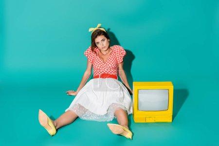 jeune pin up femme regardant caméra tandis que assis sur le sol près de jaune vintage tv sur turquoise