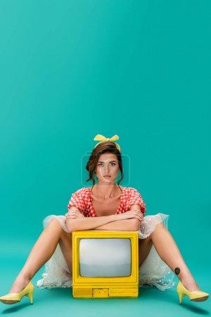 pin up femme regardant caméra tout en se penchant avec les bras croisés sur jaune vintage tv sur turquoise