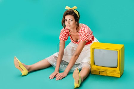pretty pin up woman sitting on floor near bright yellow vintage tv and looking at camera on turquoise