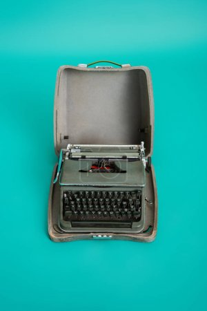 top view of vintage type machine in open case on turquoise background