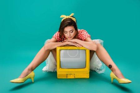 Photo pour Élégant pin up femme penché sur le jaune rétro tv set tout en étant assis sur fond turquoise - image libre de droit