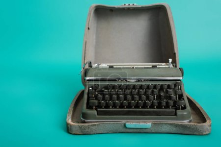 retro typewriter in open case on turquoise background