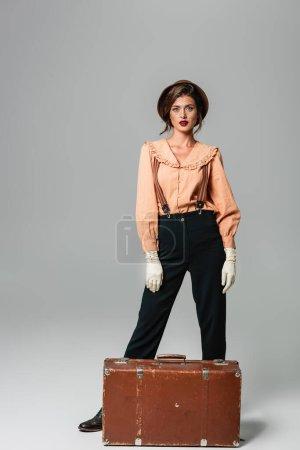 Photo pour Femme à la mode en vêtements rétro posant près de valise vintage sur gris - image libre de droit