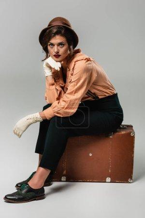 Photo pour Jeune femme en chapeau assise sur une valise vintage avec la main près du visage sur gris - image libre de droit