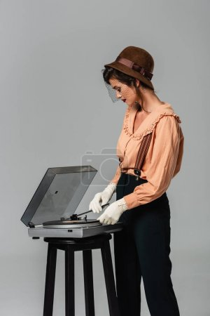 trendy woman in retro clothes turning on record player isolated on grey