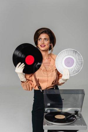 femme heureuse en vêtements vintage tenant des disques vinyle près du tourne-disque isolé sur gris