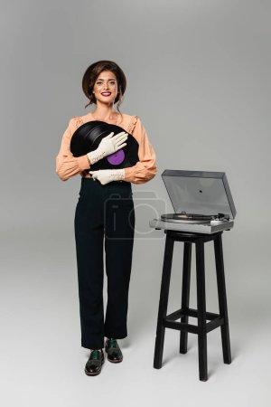 Photo pour Heureuse femme élégante en vêtements vintage tenant des disques de vinyle tout en posant près du tourne-disque sur gris - image libre de droit