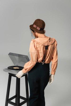 Photo pour Vue arrière de la femme en chapeau et des vêtements rétro élégants allumant le tourne-disque sur gris - image libre de droit