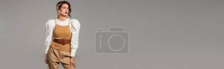 fashionable young woman in vintage clothes looking away isolated on grey, banner