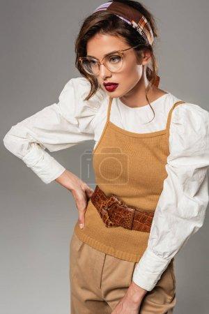 Photo pour Jeune femme à la mode en vêtements vintage posant à la main sur la hanche isolé sur gris - image libre de droit