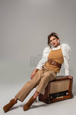 Stylische Frau in Vintage-Klamotten blickt in die Kamera, während sie auf einem Retro-Radioempfänger in grau sitzt