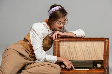 Photo pour Jeune femme en vêtements rétro tendance appuyant sur le bouton sur le récepteur de radio vintage isolé sur gris - image libre de droit