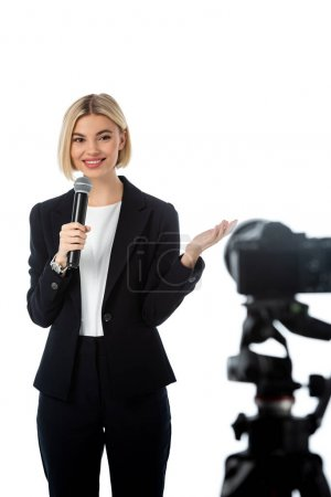 smiling blonde commentator with microphone pointing with hand near digital camera on blurred foreground isolated on white