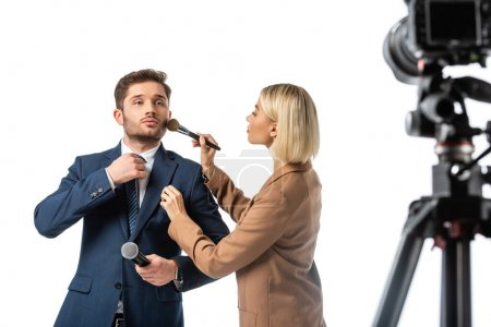 broadcaster adjusting tie while makeup artist powdering his face isolated on white, blurred foreground