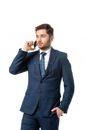 Photo for Young businessman with hand in pocket talking on mobile phone isolated on white - Royalty Free Image