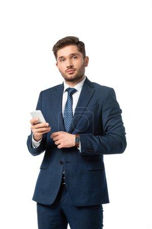 junger Geschäftsmann blickt in Kamera, während er sein Handy isoliert auf weiß hält