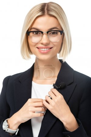 cheerful news presenter looking at camera while fixing microphone on blazer isolated on white