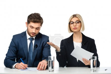 young blonde broadcaster pointing at colleague writing at workplace isolated on white