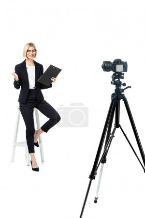 full length view of smiling news anchor on high stool pointing with hand near digital camera on tripod