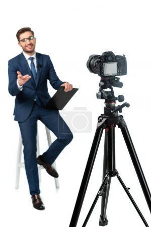 cheerful news anchor pointing with hand while sitting on high stool near digital camera on white, blurred foreground