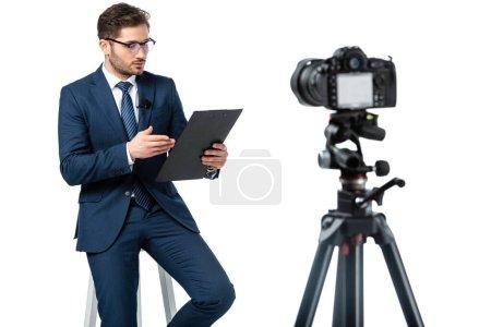 ancre de nouvelles pointant vers le presse-papiers tout en étant assis sur un tabouret haut près de l'appareil photo numérique sur l'avant-plan flou isolé sur blanc