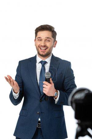 smiling journalist with microphone pointing with hand isolated on white, blurred foreground