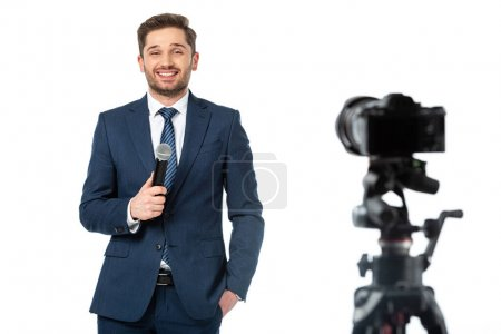 cheerful newscaster with hand in pocket holding microphone near digital camera on blurred foreground isolated on white