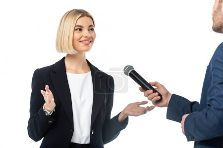 smiling blonde businesswoman talking near interviewer with microphone isolated on white