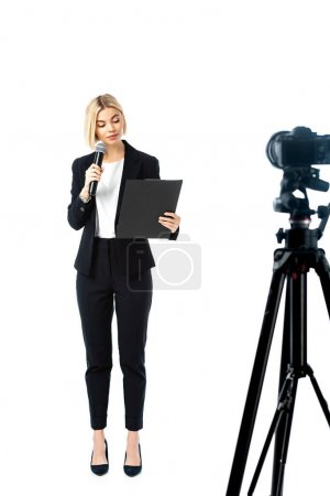 full length view of blonde news anchor in black suit near digital camera on white, blurred foreground