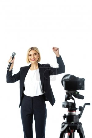 excited newscaster showing win gesture near digital camera on blurred foreground isolated on white