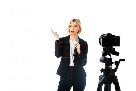 sad anchorwoman with microphone pointing with hand near digital camera on blurred foreground isolated on white
