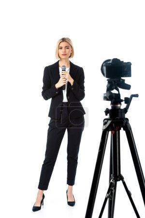 Photo pour Vue pleine longueur de l'ancre de nouvelles blondes avec microphone près de l'appareil photo numérique sur blanc, au premier plan flou - image libre de droit