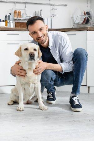 Photo pour Homme gai en jeans assis et câlin labrador à la maison - image libre de droit