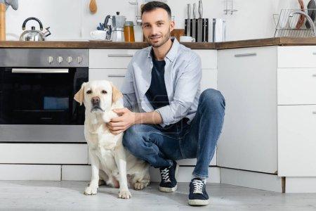 glücklicher Mann in Jeans sitzt und kuschelt Labrador zu Hause