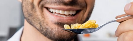 Photo for Cropped view of happy man holding spoon with corn flakes, banner - Royalty Free Image