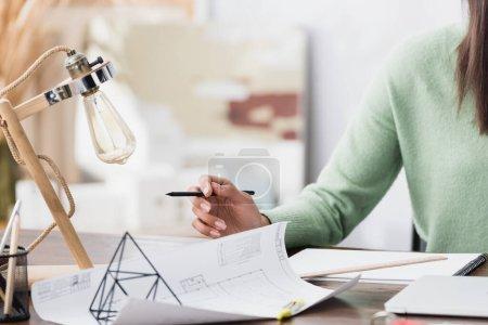 Photo pour Vue recadrée de l'architecte afro-américain tenant un crayon près du plan sur le lieu de travail - image libre de droit