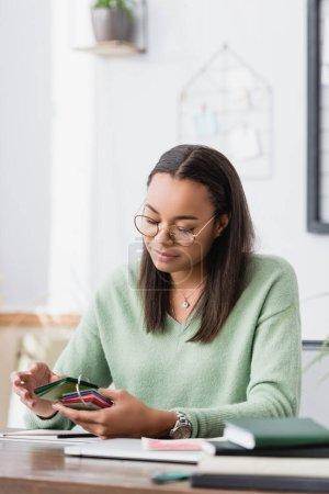 Photo pour Designer d'intérieur afro-américain souriant tenant des échantillons de matériaux sur le lieu de travail - image libre de droit