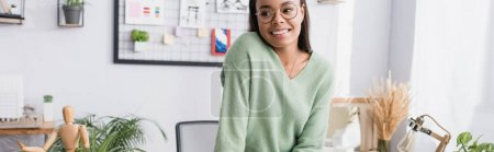 Photo for Happy african american architect in eyeglasses looking away at home, banner - Royalty Free Image