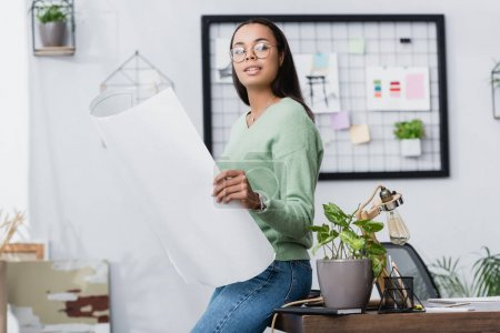 Photo for Young african american interior designer looking away while holding project near desk at home - Royalty Free Image
