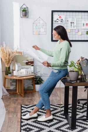 Photo pour Architecte afro-américain regardant le plan tout en s'appuyant sur le bureau à la maison studio - image libre de droit