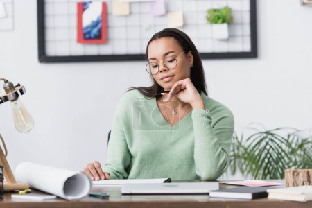 Photo for Thoughtful african american interior designer sitting at desk at home studio, blurred foreground - Royalty Free Image
