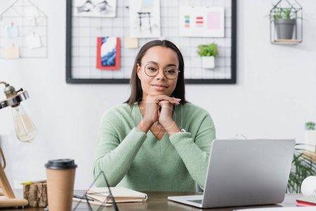 Photo pour Joyeux architecte afro-américain regardant la caméra tout en étant assis près de l'ordinateur portable et le café pour aller sur le premier plan flou - image libre de droit