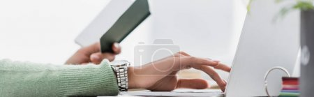 Photo pour Vue partielle d'un pigiste afro-américain tenant un carnet et tapant sur un ordinateur portable sur fond flou, bannière - image libre de droit