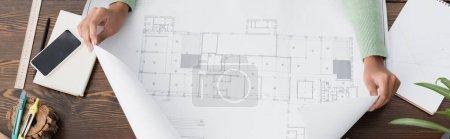 Foto de Vista recortada del arquitecto afroamericano cerca de plano y teléfono inteligente con pantalla en blanco, pancarta - Imagen libre de derechos