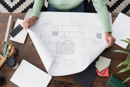 Blick von oben auf einen afrikanisch-amerikanischen Architekten, der zu Hause mit Blaupausen arbeitet